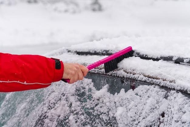 Uomo che pulisce la neve dal parabrezza dell'auto con la spazzola nella mattina d'inverno. trasporto, inverno, tempo.