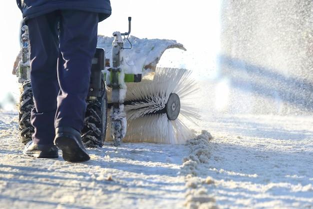Uomo che pulisce la strada da neve trattore manuale speciale