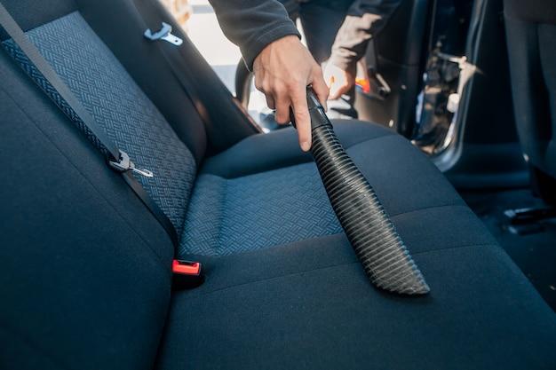 Uomo che pulisce, aspira l'interno dell'auto con un aspirapolvere, concetto di trasporto