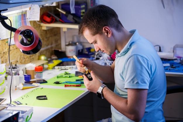 L'uomo pulisce un laptop con uno strumento speciale dalla polvere. riparazione e manutenzione di laptop e pc servizi pubblicitari per la riparazione di dispositivi elettronici e dispositivi.