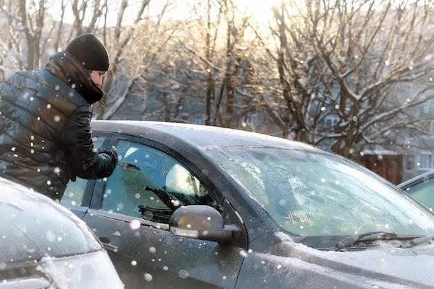 L'uomo pulisce la neve dal vetro della macchina
