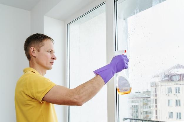 L'uomo pulisce le finestre della casa
