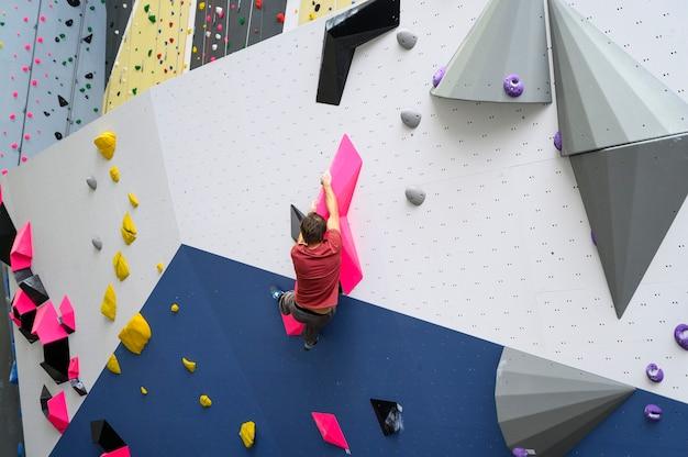 Scalatore dell'uomo sulla parete artificiale di arrampicata in palestra boulder