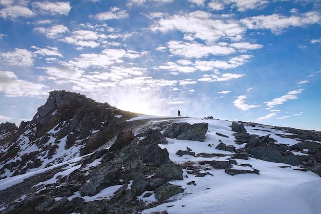 L'uomo si arrampica in cima alla montagna verso il sole nel paesaggio di ricerca.