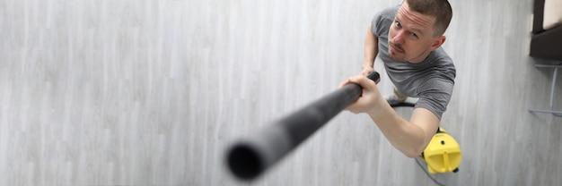 Un uomo raccoglie la polvere con il tubo dall'aspirapolvere