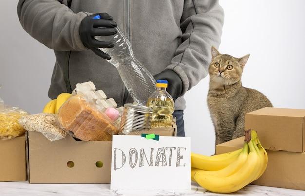 L'uomo raccoglie cibo, frutta e cose in una scatola di cartone per aiutare i bisognosi e i poveri, il concetto di aiuto e volontariato