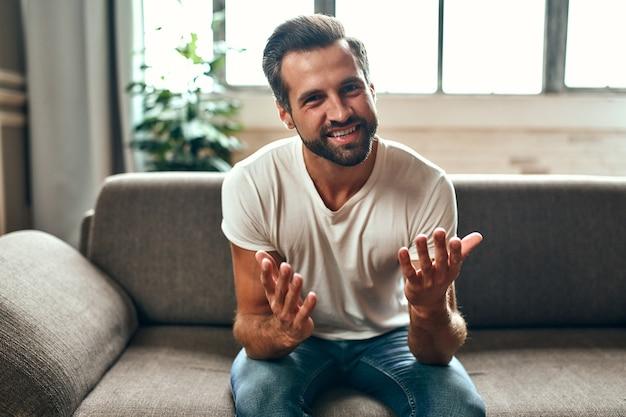 Un uomo comunica in videochiamata mentre è seduto sul divano del soggiorno di casa. lavoro da casa.