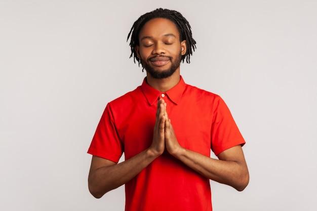 Uomo che concentra la sua mente, con gesto namaste, meditando, esercizio di yoga