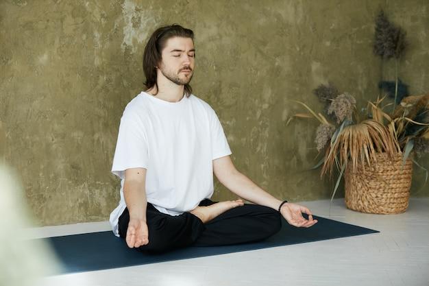 Uomo che si concentra in asana yoga a casa, bella persona che medita e cattura lo zen sul tappetino yoga