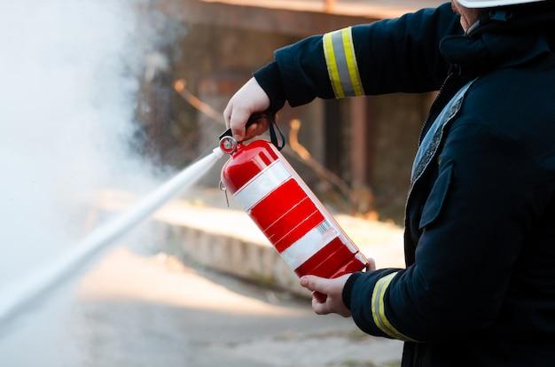 Un uomo conduce esercizi con un estintore. concetto di estinzione incendi. incidente di emergenza antincendio