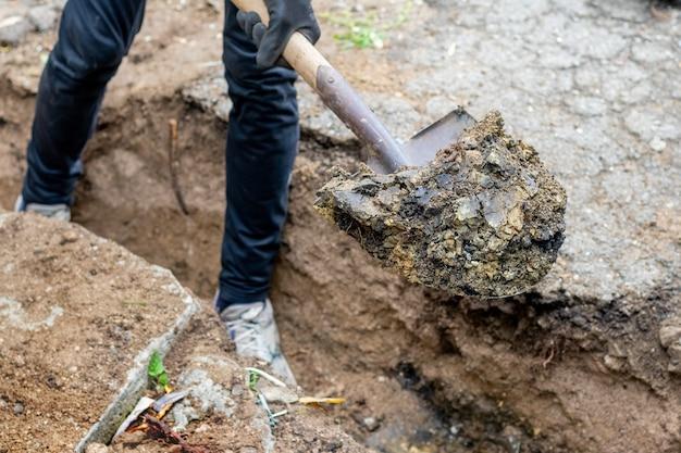Un uomo in un cantiere scava un fossato con una pala