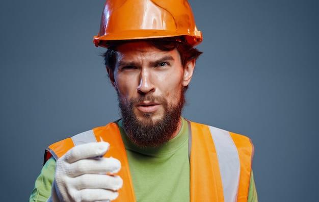 Uomo in costruzione casco arancione uniforme lavoro. foto di alta qualità