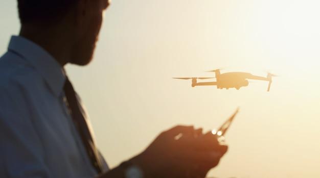 Man controll flying drone contro il tramonto