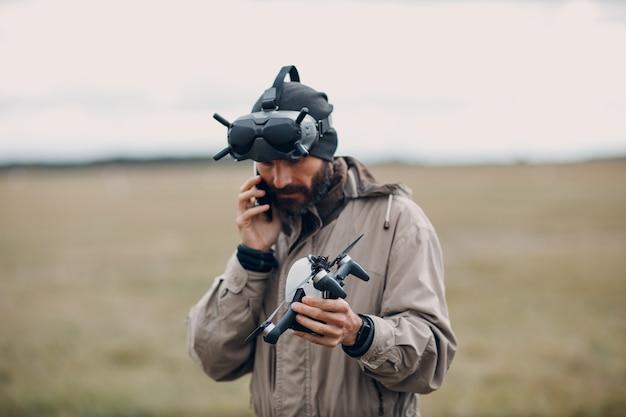 Uomo che controlla il drone quadricottero fpv per la fotografia aerea e la videografia con il telecomando dell'antenna degli occhiali.