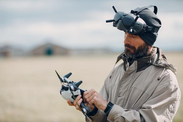 Uomo che controlla il drone quadricottero fpv con il telecomando dell'antenna per occhiali