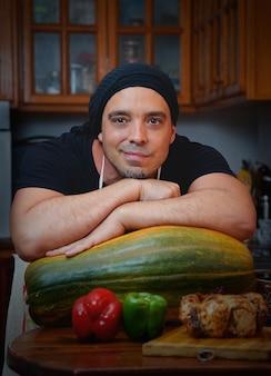 Man cook con verdure sorride a casa