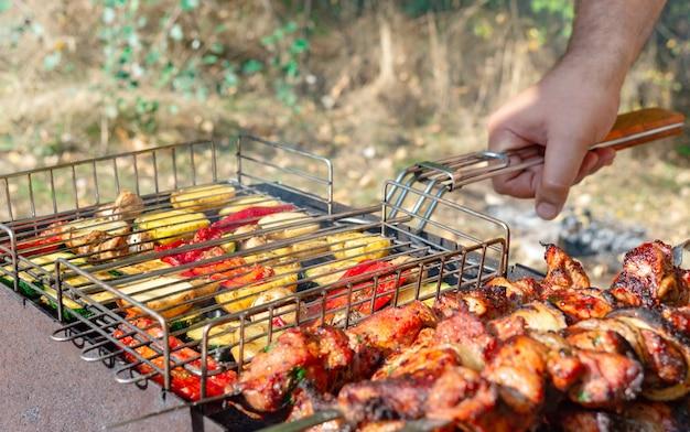 Uomo che cucina barbecue all'aperto. verdure alla griglia e carne su spiedini a fuoco aperto.
