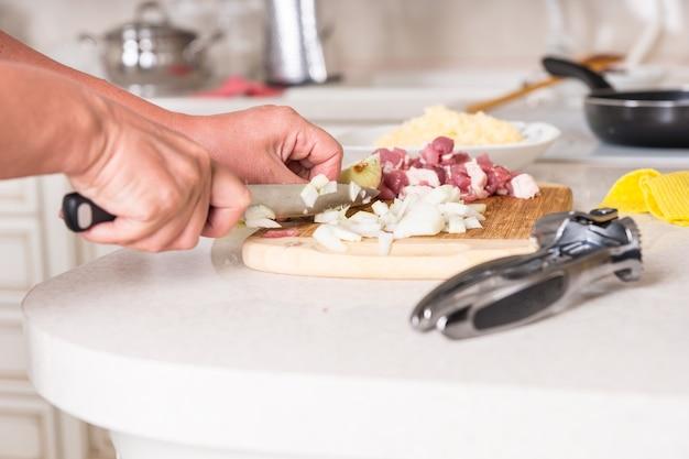 Uomo che cucina il pasto serale tritare gli ingredienti con un grosso coltello su un tagliere di legno preparare la carne e le cipolle, tritaaglio in primo piano