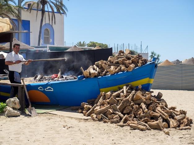 Uomo che cucina pesce sulla spiaggia di marbella