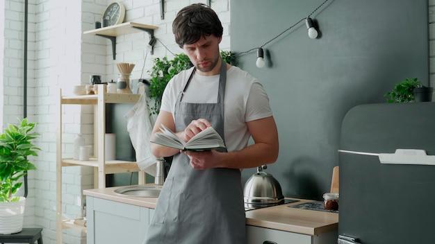 Uomo che cucina in cucina leggendo la ricetta dal libro di cucina