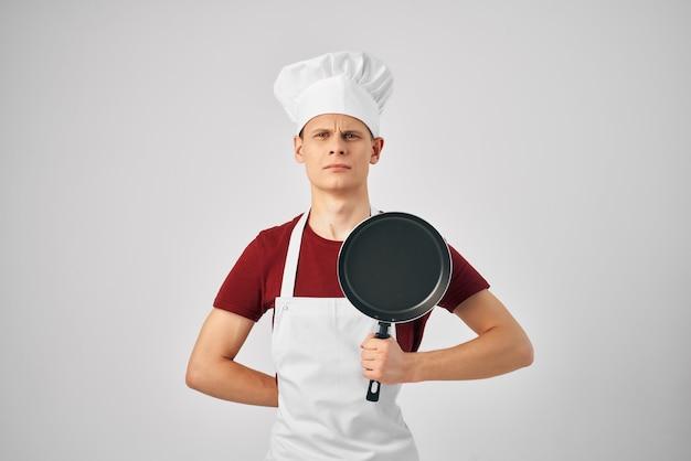 Un uomo in uniforme da cuochi una padella nelle mani di cucinare