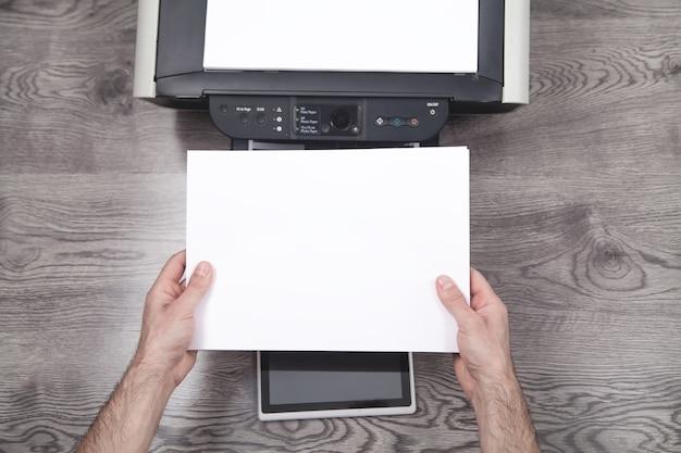 Uomo che copia e scansiona documenti in ufficio.