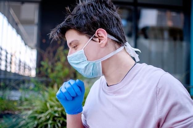L'uomo tossisce in maschera protettiva per strada, avendo allergia all'inquinamento atmosferico e dolore ai polmoni