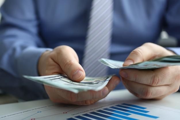 L'uomo conta cento banconote in dollari
