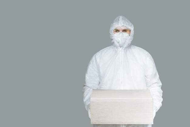 Corriere dell'uomo in una tuta protettiva e guanti da maschera con una scatola di corton.