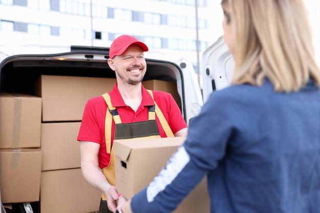 Corriere dell'uomo in uniforme che dà la scatola di carta della donna dall'automobile