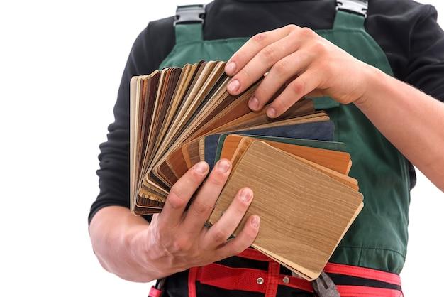 Uomo in tuta che mostra campionatore in legno isolato su bianco