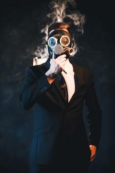 Uomo coperto di fumo e con indosso una maschera antigas. influenza pericolosa della dipendenza dal fumo. concetto di pericolo per la salute