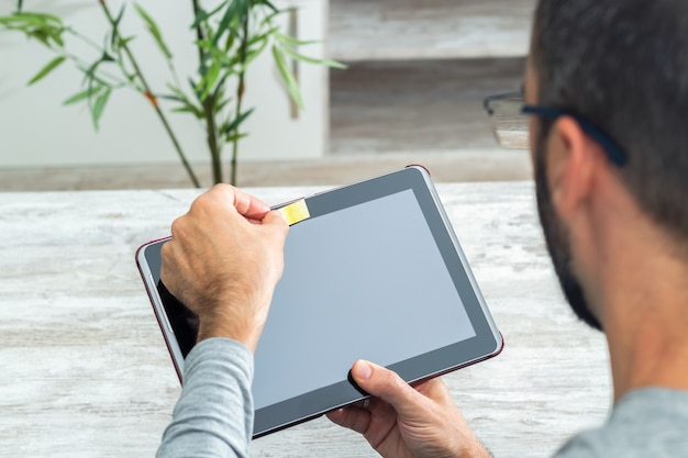 Uomo che copre la fotocamera del tablet con una carta