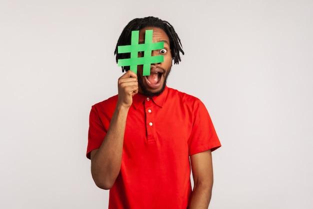 Uomo che copre il viso con il simbolo dell'hashtag dei social media, consiglia di seguire contenuti alla moda, blog.
