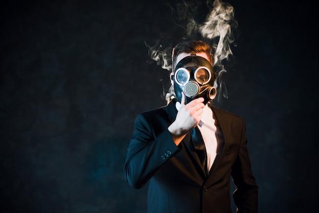 Uomo che si copre il viso con una maschera antigas circondata da fumo di nicotina. pericolo di essere un concetto di fumatore passivo Foto Premium