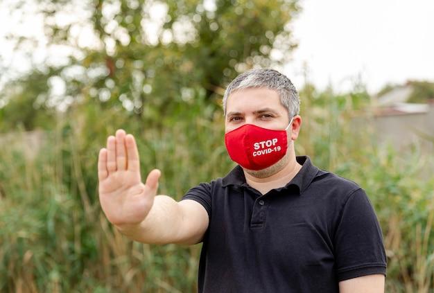 Uomo che copre il viso con maschera protettiva per la protezione dai virus
