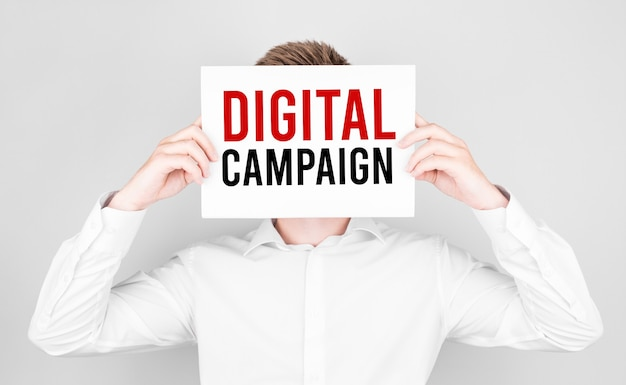 L'uomo si copre la faccia con un libro bianco con il testo campagna digitale
