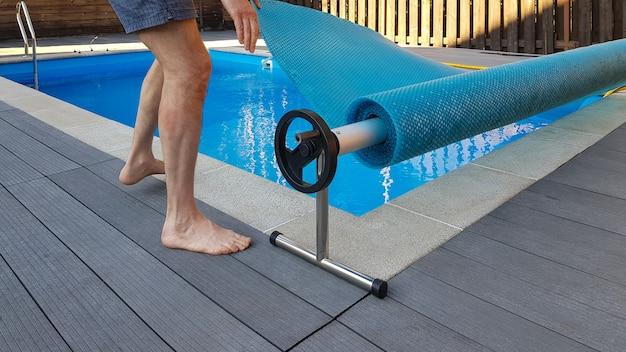 L'uomo copre la piscina con copertura per la protezione