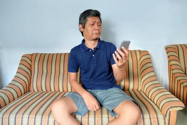 L'uomo piange mentre guarda lo schermo del telefono