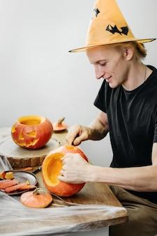 Uomo che curva la zucca di jac o lanten helloween a casa