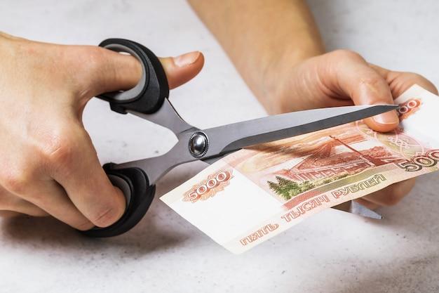 Un uomo taglia il concetto di cinquemila rubli russi sul tema della svalutazione del denaro nel paese