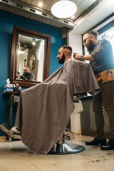 L'uomo taglia i capelli al negozio di barbiere