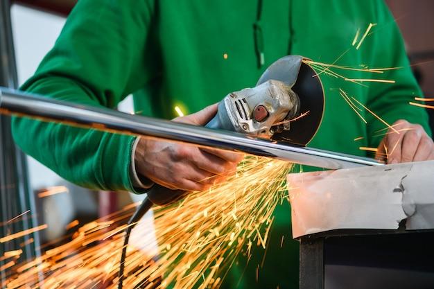 Un uomo taglia parte di un tubo con una smerigliatrice. l'uomo taglia parte del tubo con una smerigliatrice. vista dal basso..