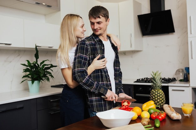 L'uomo taglia il pepe mentre sua moglie lo abbraccia da dietro