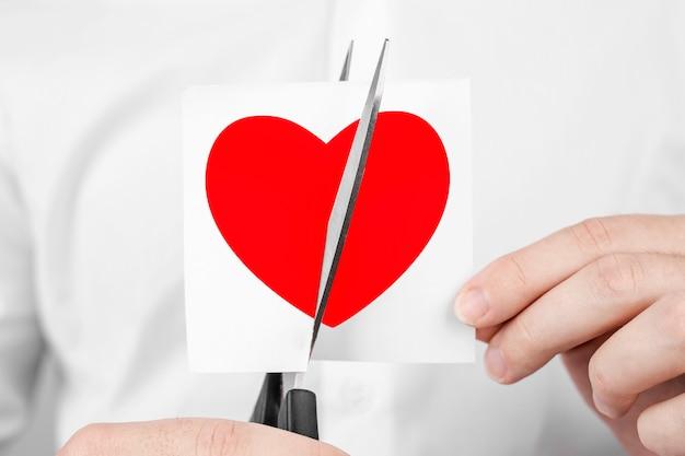 L'uomo taglia adesivo forbici con cuore rosso