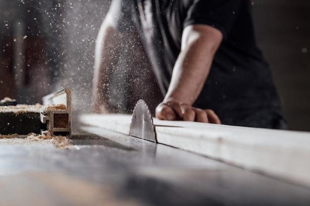 Un uomo taglia il legno su una sega circolare in una falegnameria