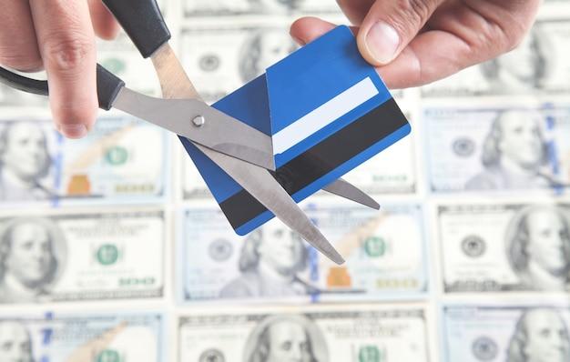 Uomo che taglia la carta di credito con le forbici.