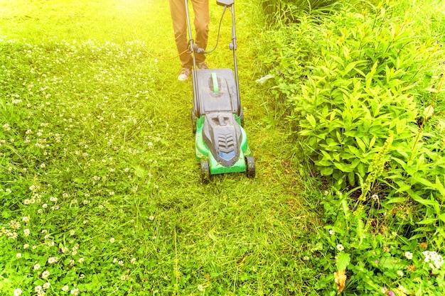 Uomo che taglia erba verde con tosaerba in cortile. fondo di stile di vita del paese di giardinaggio