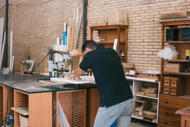 Uomo che taglia un pezzo di legno con una taglierina elettrica in un'officina