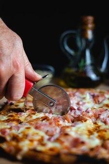 Un uomo che taglia una pizza usando un tagliapizza. ci sono origano e olio d'oliva in background. (verticale)